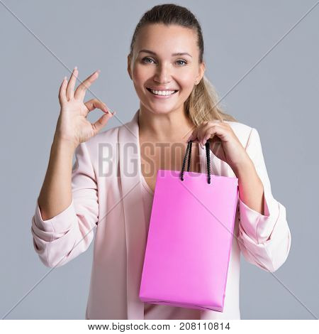 Portrait of a smiling woman with shopping bag and with okay sign. Attractive cheerful female holds the  bag with purchasing.