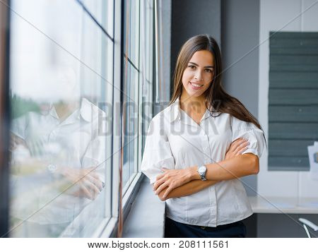 Portrait of attractive business woman posing on a blurred office background. Confident manager girl in stylish formal wear. Copy space.
