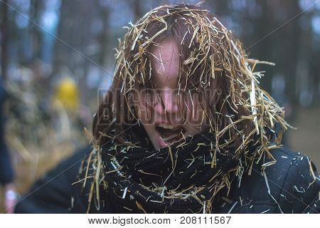 Zhytomyr Ukraine - January 19 2016: Young woman with lovely long curly hair standing outdoors blowing her nose in an urban square due to a seasonal cold or hay fever
