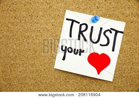 A Yellow Sticky Note Writing, Caption, Inscription Phrase Trust Your Heart In Black Ext On A Sticky