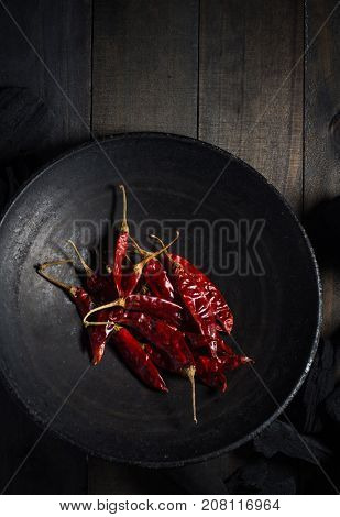 Dried red hot Indian chilies in a dark metal wok on wooden background. A rustic food photography background. View from above.