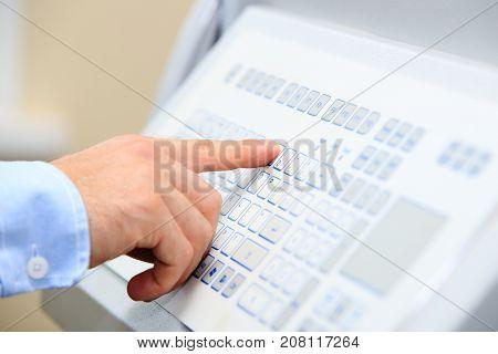 Engineer hand on industrial keypad closeup. Engineer fixes power equipment with new modern keypad.