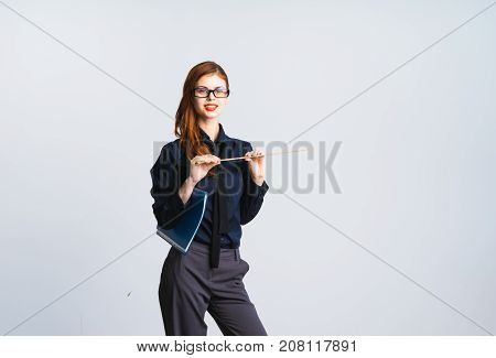 a cute red-haired girl with glasses and a black shirt is holding a folder and ruler in his hands and looking into the camera