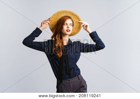 girl in black shirt with hat on head posing against white background