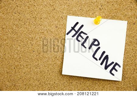 A Yellow Sticky Note Writing, Caption, Inscription Phrase Help Line Help Line In Black Ext On A Stic