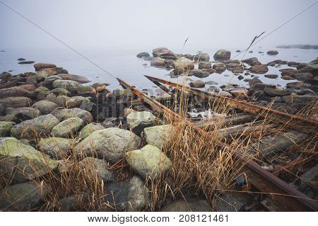Stony coast of the Baltic Sea. Rails for launching ships into the water. Foggy spring morning. Leppneeme sadam. Estonia
