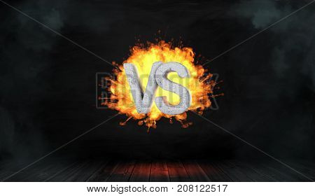 3d rendering of a dark background with a concrete lettering VS hanging in the center of an orange fire blast. Business and confrontation. Conflict. Fight against opponent.