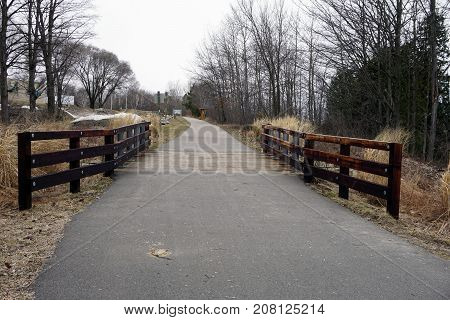 BAY VIEW, MICHIGAN / UNITED STATES - MARCH 30, 2017: A bridge, along the Little Traverse Wheelway, which connects Charlevoix, Petoskey and Harbor Springs, Michigan, allows hikers and bicyclists to cross Tannery Creek, near the Tannery Creek Trailhead.