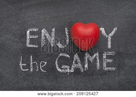 enjoy the game phrase handwritten on blackboard with heart symbol instead of O