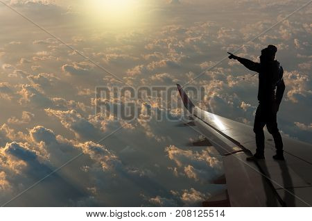 silhouette of man who pointing the sun with clouds on airplane wing Challenge business concept, 3D illustration