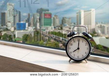 Vintage alarm clock at windows with abstract Blurred photo of sky train with traffic jam on early morning traffic tranportation concept