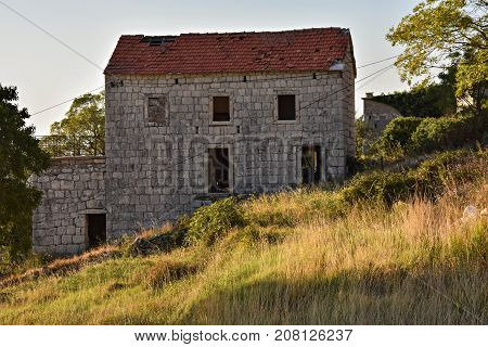 Abandoned ruin house whit red roof at countryside field