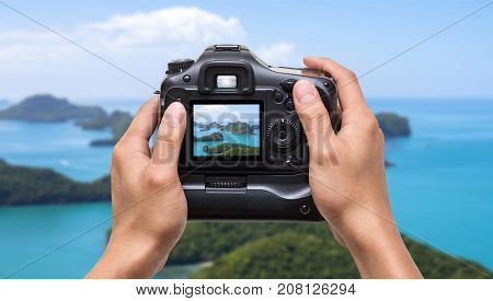 Hands holding the camera which taking photo of Top view of Ang Thong National Marine Park with rainbow Thailand