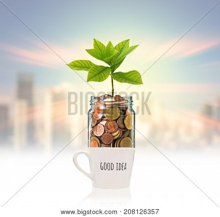 Gold coins and seed in clear bottle over the glass with text good idea on photo blurred cityscape backgroundBusiness investment growth concept, 3D