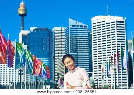 SYDNEY - AUGUST 16 2017:Chinese tourist looking at camera in front of the Pyrmont Bridge at sunset in Darling Harbour a recreational and pedestrian precinct western to Sydney central business district in New South Wales Australia