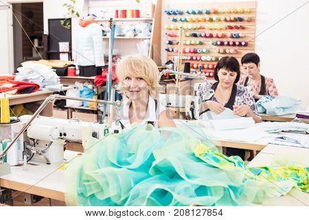 Seamstresses sews dresses in atelier studio. Seamstresses working.