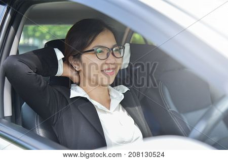 Relaxed Asian Business girl in glasses holding hands behind head while is in a car. Success and Happy Concept. Smiling face.