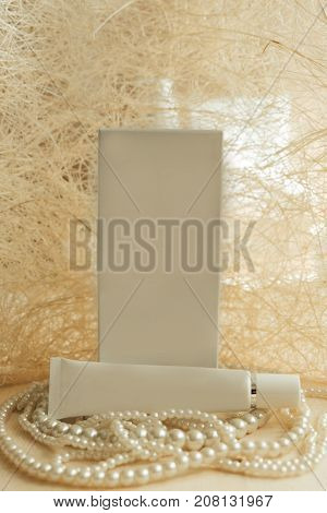 Front View. Package And Cream Placed On Luxury Pearl Necklace Have White Abstract Material Are Backg