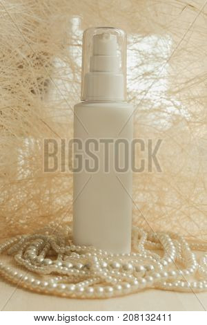 front view. white bottle cream placed on luxury pearl necklace have white abstract material are background. image for skin care cosmetic makeup women beauty art concept