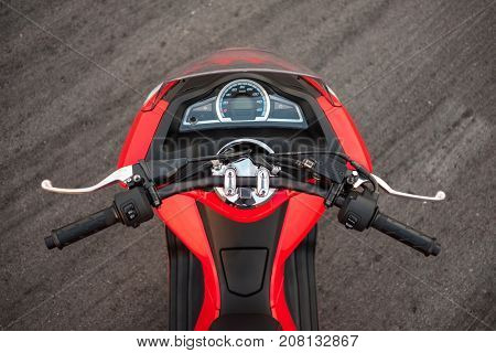 top of red motorcycle nobody are ride with interface status Chassis motorcycle handlebars. has concrete are background. image for vehicle motorcycle sport fashion concept
