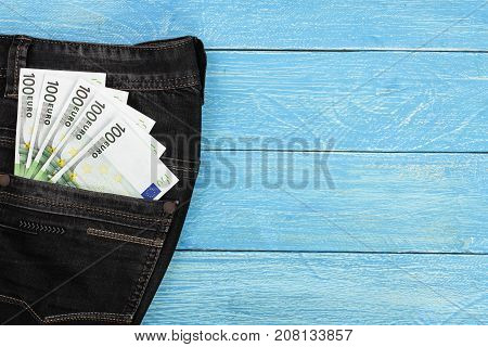 one hundred euro banknotes in a jeans pocket on blue wooden background with copy space for your text. Top view.
