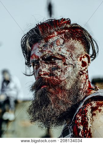 Halloween war soldier with wounds on face. Vampire hipster with red blood outdoors. Zombie on roof on blue sky. Holiday celebration concept. Man with bloody beard and hair.
