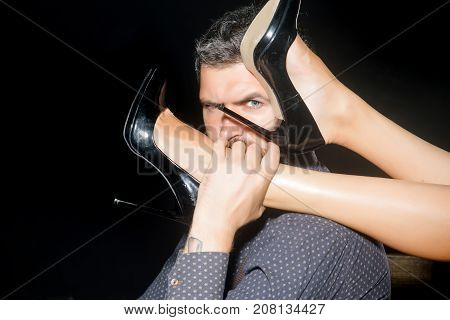 Romance and couple in love. Legs of woman in shoes at man with beard. Guy at table with female legs. Love and relations dominating. Man in shirt isolated on black background.