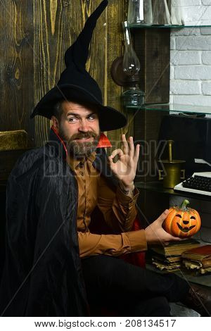 Halloween Wizard Smiling With Pumpkin On Wooden Wall