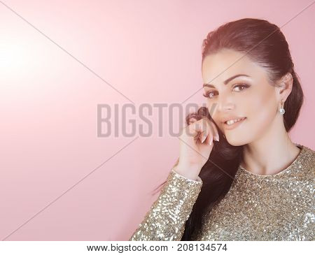 Woman smiling on pink background. Girl with brunette hair in dress of golden sequins. Holidays birthday new year christmas anniversary celebration. Fashion and style. Beauty and makeup copy space