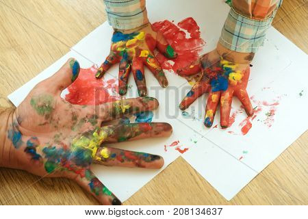 Hands and fingers drawing with multicolor paints on white paper. Handprint painting concept. Arts and crafts. Imagination creativity and freedom. Fathers day family love and care.