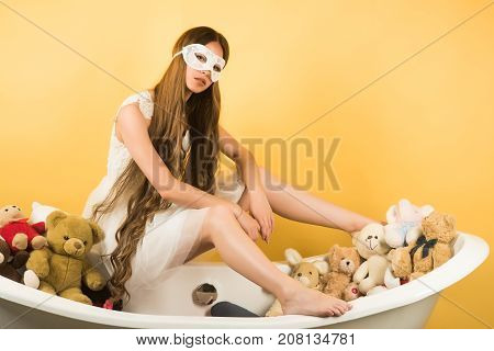 Beauty salon and wedding fashion. bath with toy bear and girl in white dress. Hairdresser and spa relax. Woman with long hair white dress and crown. Girl in mask sit on bath tub on yellow background.