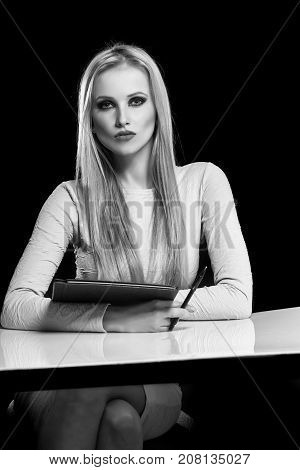 Portrait of one attractive elegant sensual serious young blonde business woman with long hair in pink dress sitting at white table holding brown folder and pen on black background vertical picture