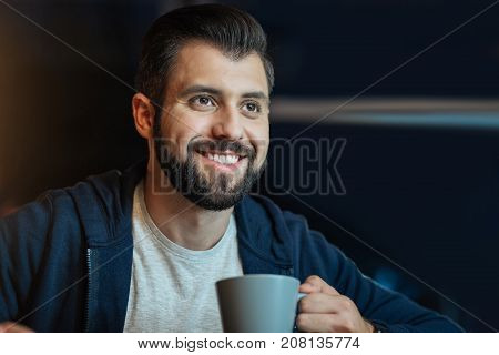 Feeling happiness. Positive office worker holding cup in left hand and looking forward while sitting at his workplace