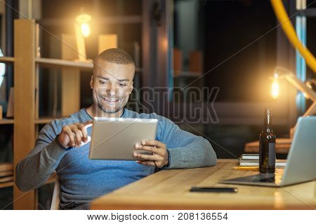 Do it quickly. Young man expressing positivity and leaning elbow on table while being very attentive