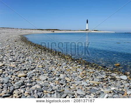 Gravel beach on Ile de Sein (France) with lighthouse in the background