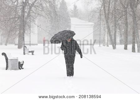 Bad weather in winter: a heavy snowfall and blizzard in city. Male pedestrian hiding from the snow under umbrella