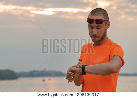 Urban jogger looking at his watch after exercising.