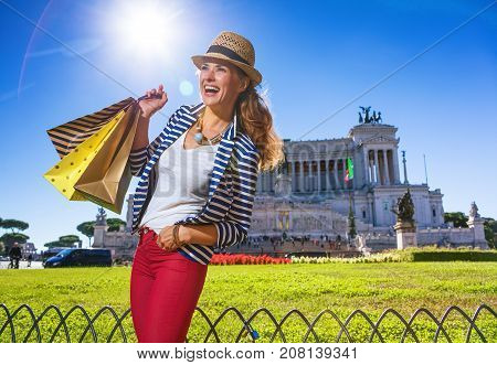 Roman Holiday. smiling trendy traveller woman in Rome Italy with shopping bags looking into the distance
