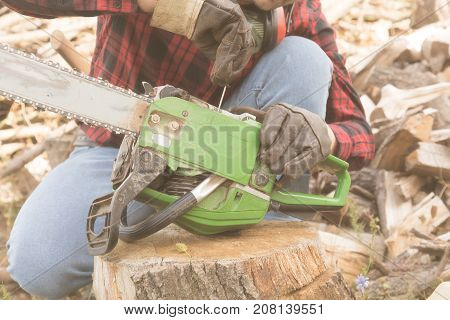 Lumberjack fixing the chainsaw with cut woods around him.