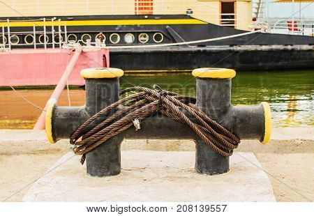 Mooring rope tied to the bollard at the pier. Nautical mooring rope. Boat moored by the river