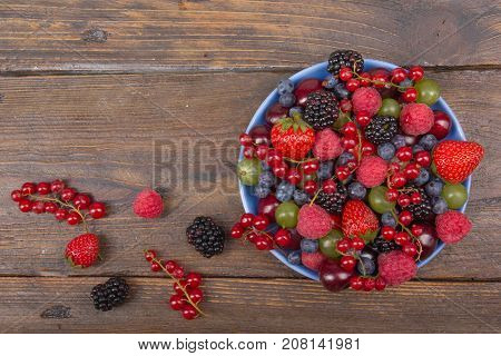 Various summer Fresh berries in a bowl on rustic wooden table. Antioxidants, detox diet, organic fruits