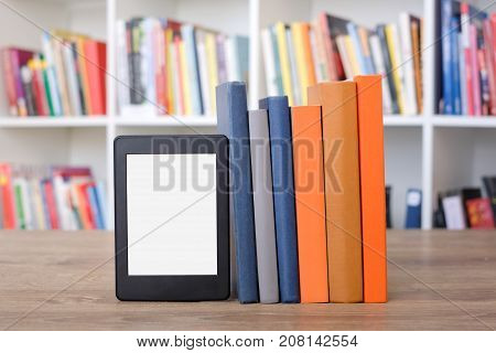 E-book reader and colorful bookshelf as background