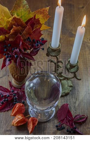 on a wooden surface a transparent globe for divination and maple leaves