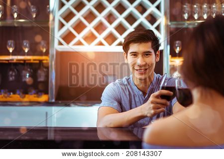 Young asian couple together man and woman clink glasses drink wine cocktail in bar luxury party celebration clam relaxing in nightclub at pub Closeup male and copy space the left.
