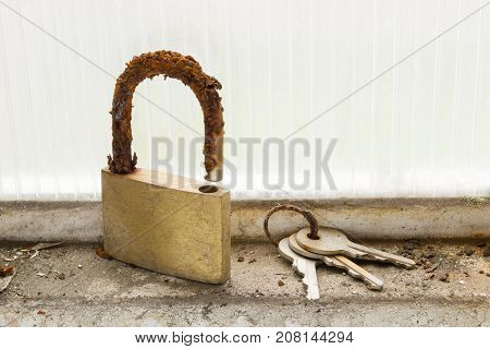 a lock and a set of keys look totally deteriorated and unusable due to the effect of the humidity and corrosion to which they were exposed when being abandoned in a window of a garage