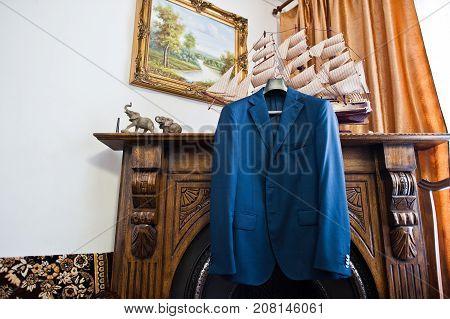 Groom's Elegant Blue Wedding Tuxedo Hanging On The Racks On The Commode In The Room.