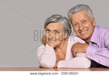 Elderly woman and man sitting at wooden table and hugging