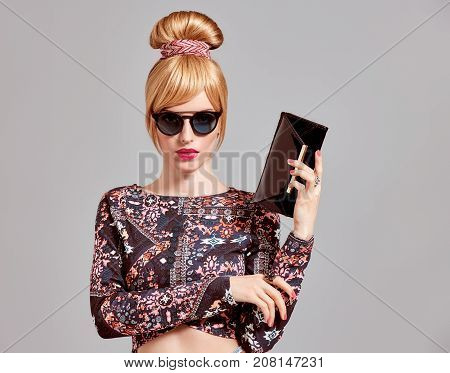 Fashion. Young Woman in Glamour Sunglasses, Stylish Hairstyle, fashion Autumn Outfit. Sexy model Girl, cheeky Emotion. Beautiful Blond Woman with Trendy Glamour Handbag Clutch, fashion pose