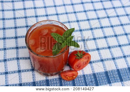 Glass of freshly squeezed tomato juice on towel background