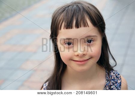 Cute smiling down syndrome girl in the city.